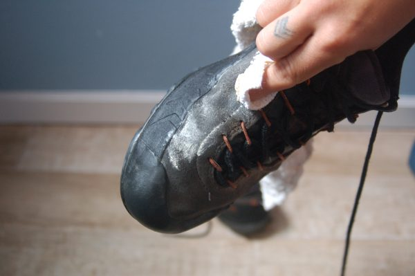 person waterproofing boots