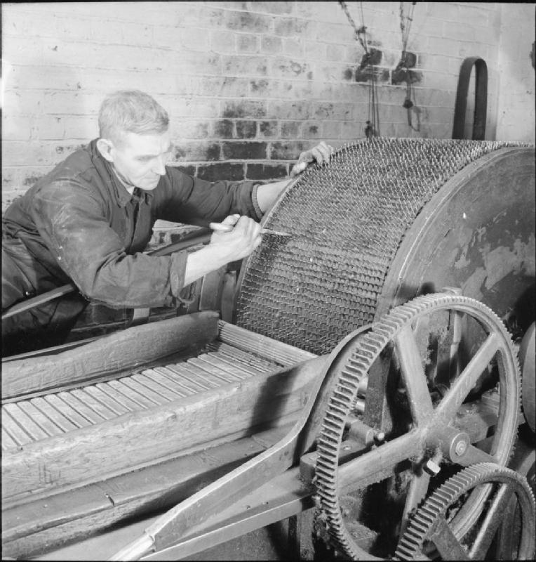 An engineer at this textile mill sets the teeth of the rag grinding machine