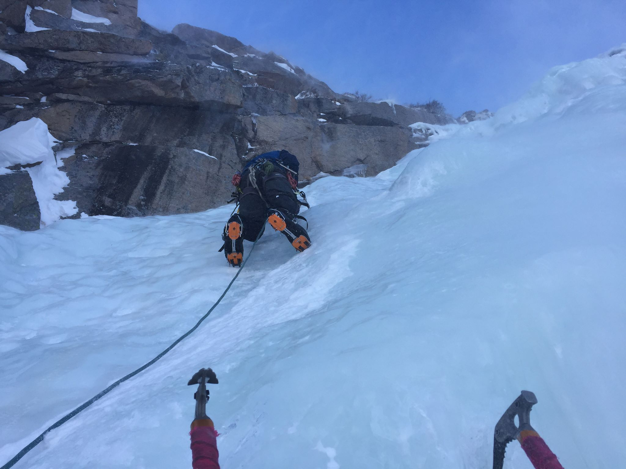 person climbing with crampons