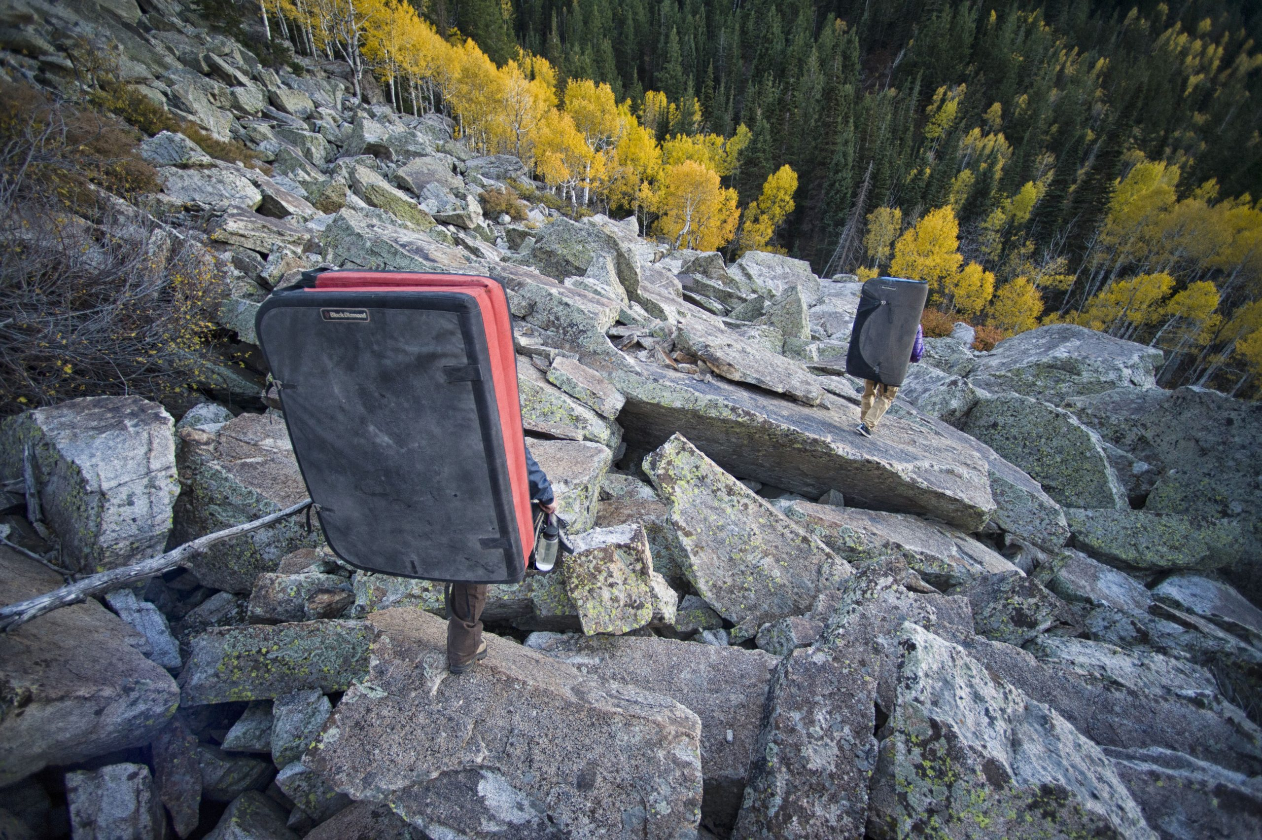 Two athletes hiking the wasatch mountains with climbing crash pads