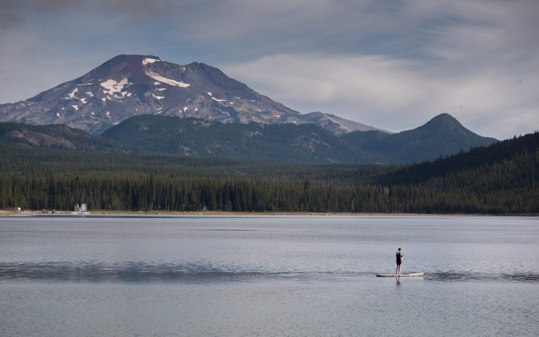 woman paddle boarding in mountain lake