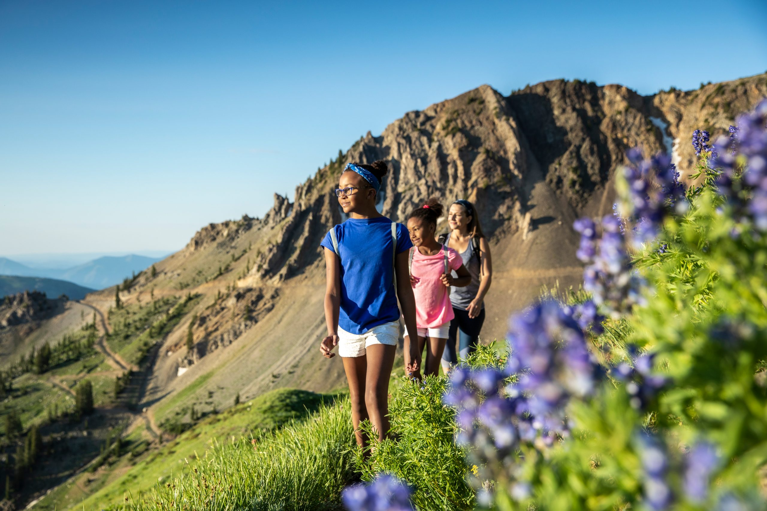 two girls and a woman hiking in a spring trail of flowers