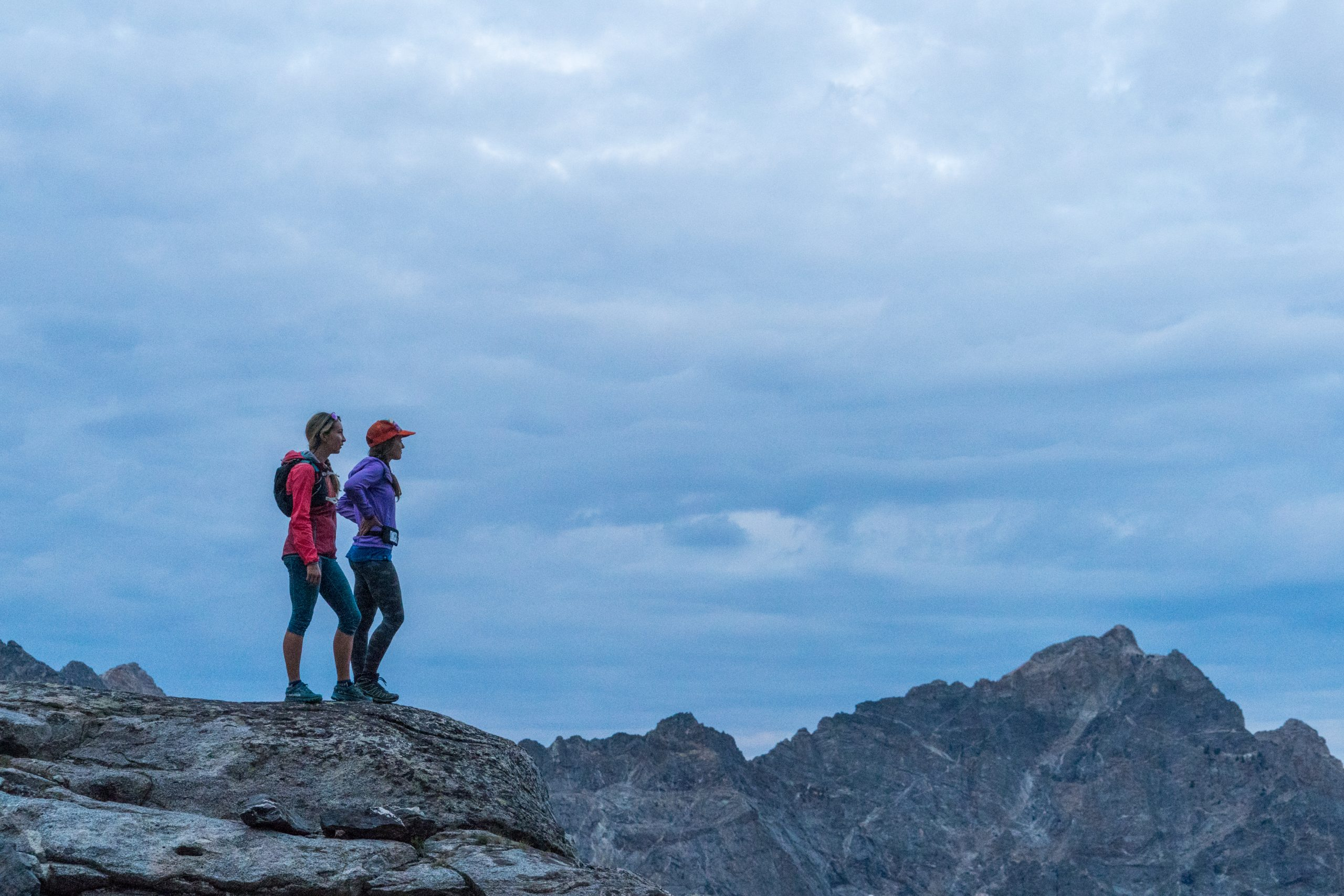 two women overlooking the edge of a summit